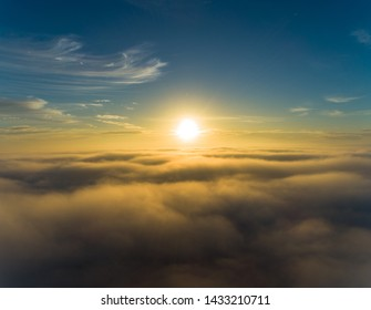 Winter sunrise above clouds and thick fog