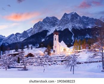 winter sunrise behind beautiful church in the mountains - Grainau village, Bavaria