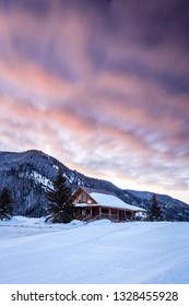 Winter sunrise clouds above a log cabin in the Utah Mountains, USA.