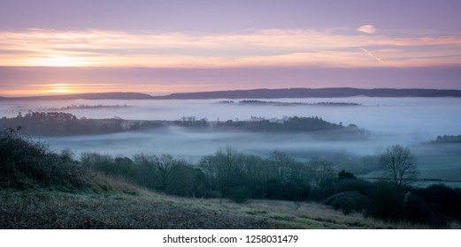 Winter sunrise at Newland's Corner, a beauty spot in the North Downs, Surrey, UK, on a foggy morning