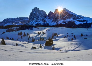 Winter sunrise on Alpe di Siusi with rising sun over Sassolungo and Sassopiatto, Dolomites, Italy