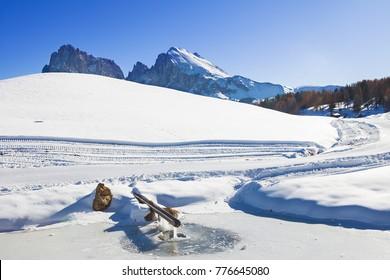 Winter sunrise on Alpe di Siusi with rising sun over Sassolungo and Sassopiatto, Dolomites, Italy