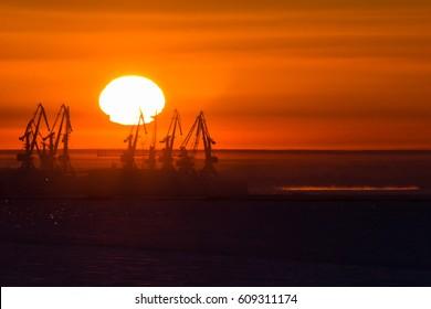 Winter sunrise over frozen river and port cranes