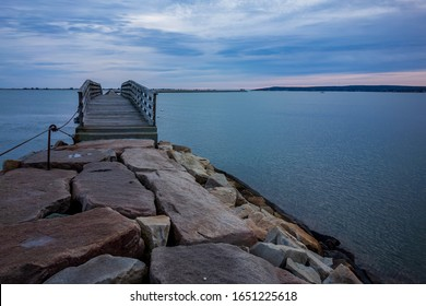 Winter sunrise at Plymouth's stone jetty & wooden bridge in the harbor - Plymouth, Massachusetts.