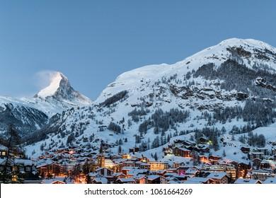 Winter sunrise view on snowy Matterhorn, blue sky and Zermatt village, Switzerland.