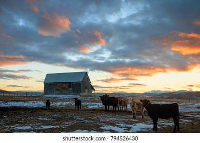 Winter sunset with barns in rural Utah, USA.