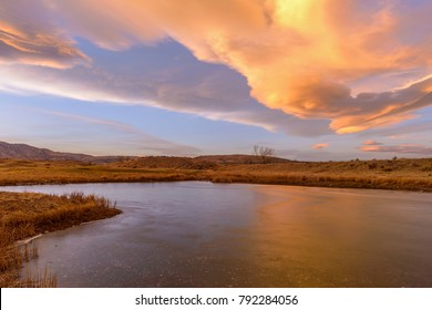 Winter Sunset Clouds - Colorful sunset clouds rolling over a frozen mountain lake at foothill of front range of Rocky Mountains. Bear Creek Park, Denver-Lakewood, Colorado, USA.