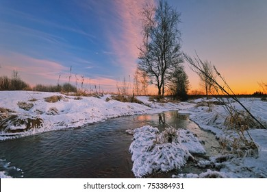 Winter sunset in winter field with small river