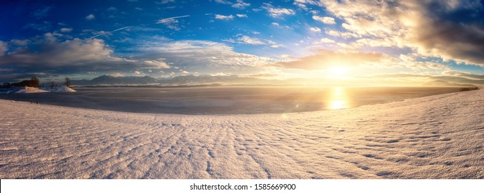 Winter sunset landscape with lake, snowy bank, mountains on background, blue sky with clouds and sun. Liptovska Mara, largest water reservoir (dam) in Slovakia (Slovensko), large panorama
