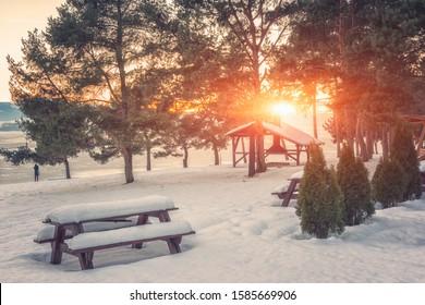 Winter sunset landscape with lake, snowy bank, trees and sun at rest zone. Liptovska Mara, largest water reservoir (dam) in Slovakia (Slovensko), travel background of popular tourist destination