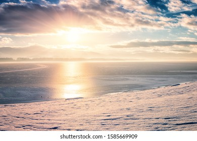 Winter sunset landscape with lake, snowy bank, mountains on background, blue sky with clouds and sun. Liptovska Mara, largest water reservoir (dam) in Slovakia (Slovensko), tourist destination