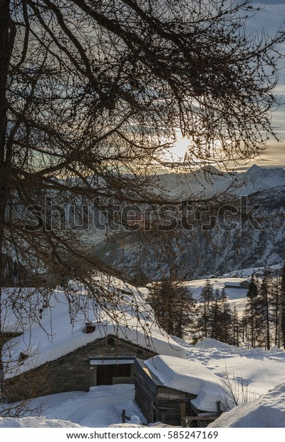 Winter sunset in the mountains (Ayas Valley, Monte Rosa Massif, Italy), with mountain huts in the foreground.