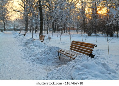 Winter sunset on the alley in the old park. Trees and benches in the city park are covered with an abnormally large snow.