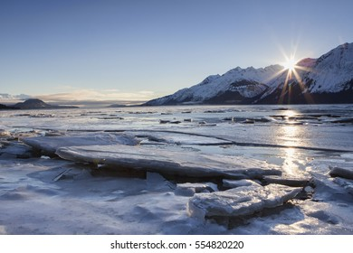 Winter sunset on the Chilkat Estuary beach near Haines in Southeast Alaska with an outgoing tide stranding floating slabs of ice.