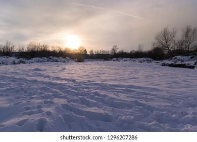 winter sunset over the frozen river shore