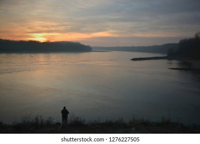 Winter sunset over junction of Morava and Danube rivers near Bratislava, Slovakia framed with floodplain forest and with lone angler in the foreground.