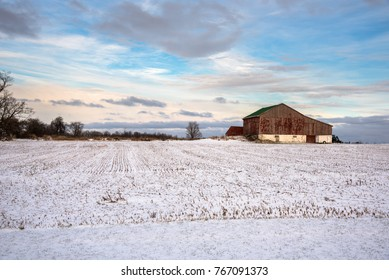 Winter Sunset over a an Old Barn in a Snowy Field in the Countryside of Ontario, Canada.