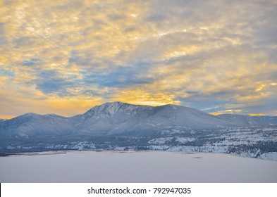 Winter Sunset over a snow covered Columbia Lake looking at the Purcell Mountains, British Columbia, Canada