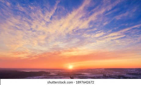 Winter sunset rural Skyscape - Stunning epic sunset sky with the setting sun on the horizon. Pink-orange winter frosty sunset against a bright blue sky with Spindrift clouds.