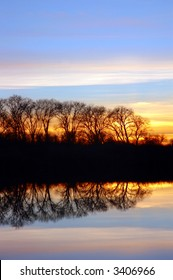 Winter Sunset and Silhouette of Oak Trees Reflected in Wildlife Pond, San Joaquin Delta, California