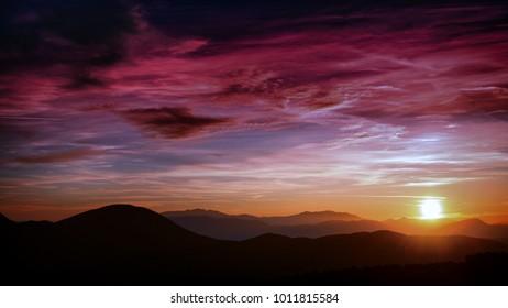 winter  sunset sky with purple clouds over an orange horizon