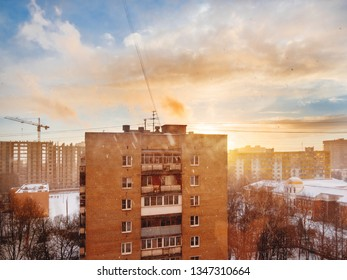 Winter sunset with snowfall. Cloudscape with sun rays upon Odintsovo town, Russia.