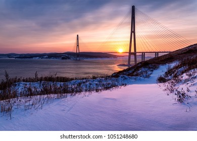 Winter sunset view with fresh snow and long cable-stayed bridge in Vladivostok, Russia