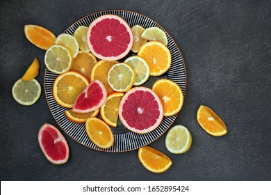 Winter sunshine health food of citrus fruit with oranges, lemons & grapefruit on grey grunge background & round plate. High in antioxidants, vitamins, dietary fibre and anthocaynins. Top view.