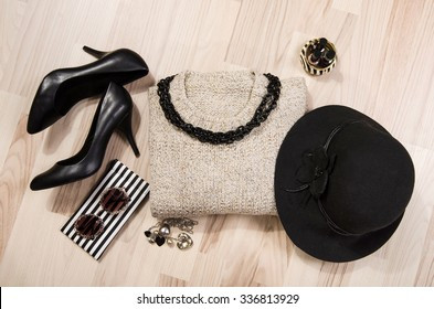 Winter sweater and accessories arranged on the floor. Woman sweater with silver accessories, high heels, black hat, necklace and nail polish.