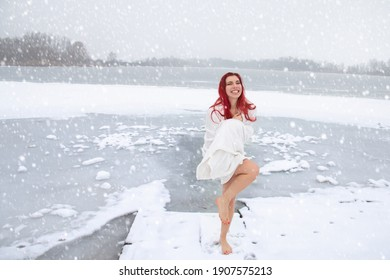 Winter swimming and cold water immersion. Pretty cheerful woman wrapped in a towel is hardening outdoors on snow at icy frozen lake landscape