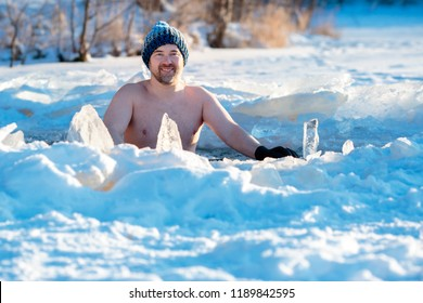 Winter swimming in frozen lake. Man in an ice-hole. Healthy lifestyle