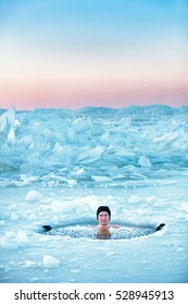 Winter swimming in frozen sea. Man in an ice-hole. Healthy lifestyle
