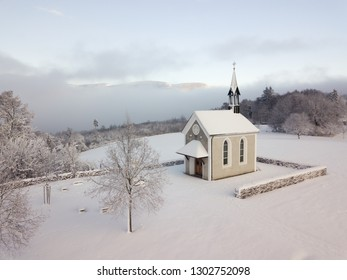 Winter Switzerland Landscape of small chapel on hill with fresh snow looking as if in a fairytale (Cinderella)
