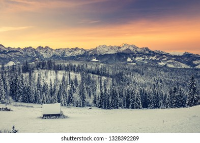 Winter Tatra mountains landscape with wooden hut at dawn