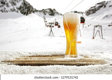 Winter time in Alps and beer in glass with free space for your bottle