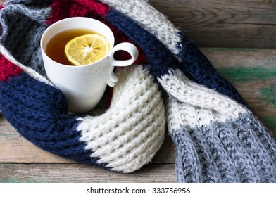 Winter time: cup of hot tea with lemon and scarf on rustic background
