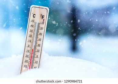 Winter time. thermometer on snow shows low temperatures