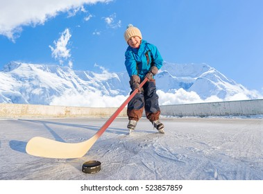 Winter time. Young happy child playing ice hockey on an outdoor ice rink. Focus on the boy.