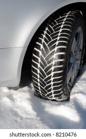 winter tire, tread filled with snow, on car with silver colored fender