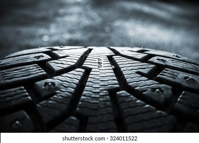 Winter tires photographed in close-up view in Finland. Focus point is in the center of the numbers. The front and back out of focus. Image includes a heavy effect.