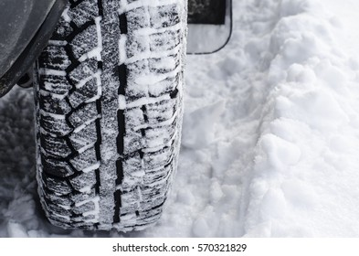 winter tires with spikes on snow-covered road