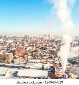 Winter town. Frosty sunny day in the city. Snow on the streets and smoke from the boiler rises. Frost and sun, a wonderful day.