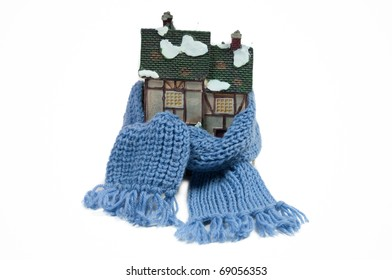 Winter toy half-timbered house wrapped in a shawl isolated on white background