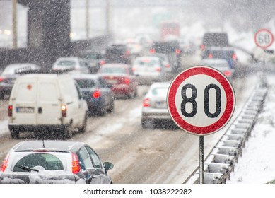 Winter traffic jam during snowstorm with poor visibility. Speed limit sign with a traffic jam in the background on a slippery highway covered with snow