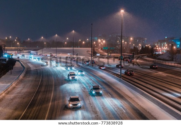 Winter Traffic on Snow Covered Highway Curve in City during Snowstorm