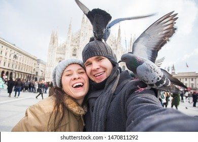 Winter travel and vacations concept - Happy tourists taking a self portrait with funny pigeons in front of Duomo cathedral in Milan