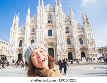 Winter travel, vacations and holidays concept - Young happy woman touris making selfie photo in front of the famous Duomo cathedral in Milan.