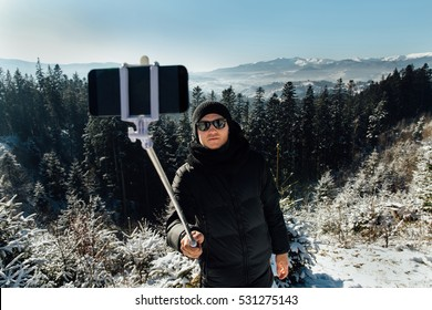 Winter travel, young boy in winter wear and sunglasses make selfie photo with selfie stick on winter forest background