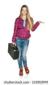 Winter traveler. Smiling young female in winter coat in full length standing with the old fashioned suitcase holding blank copy space on her open palm , isolated on white background