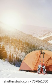 Winter trek in the mountains. The tent stands on the mountainside against the backdrop of the mountains.